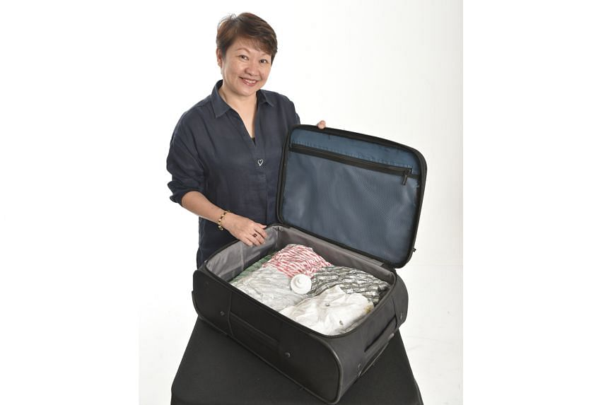 Madam Linda Chan uses a Vago baggage compression device to remove air trapped within clothes and compress soft items in a vacuum bag.
