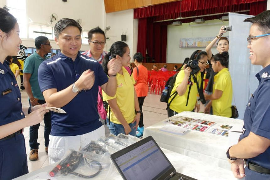 MP for Bishan-Toa Payoh GRC Saktiandi Supaat checks out bicycle tags at the Singapore Police Force's booth during the Road Safety Awareness Day event at Toa Payoh East Community Club on March 18, 2018.