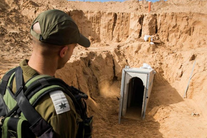 A picture taken from the Israeli side of the border Gaza Strip border shows an Israeli army officer walking near the entrance of a tunnel, which Israel says was dug by the Islamic Jihad group, leading from the Palestinian enclave into Israel, on Jan