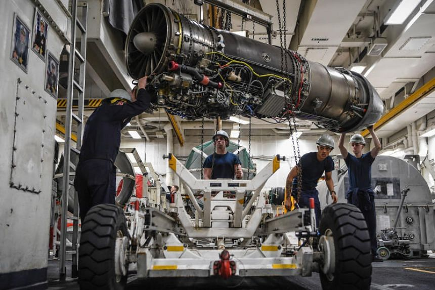 Sailors lowering a jet engine on board the aircraft carrier USS Theodore Roosevelt on Feb 26, 2018. Smugglers are attempting to ship US technology at rates that could outpace the Cold War, say experts.
