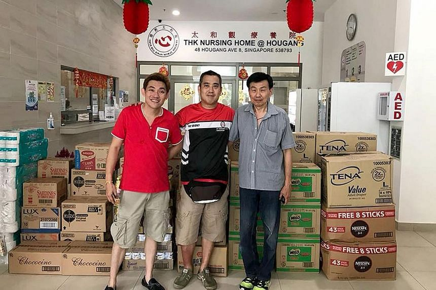 Taxi drivers (from left) Patrick Tan, Admen Lim and Albert Khoo, with the donated goods at the Thye Hua Kwan Nursing Home.