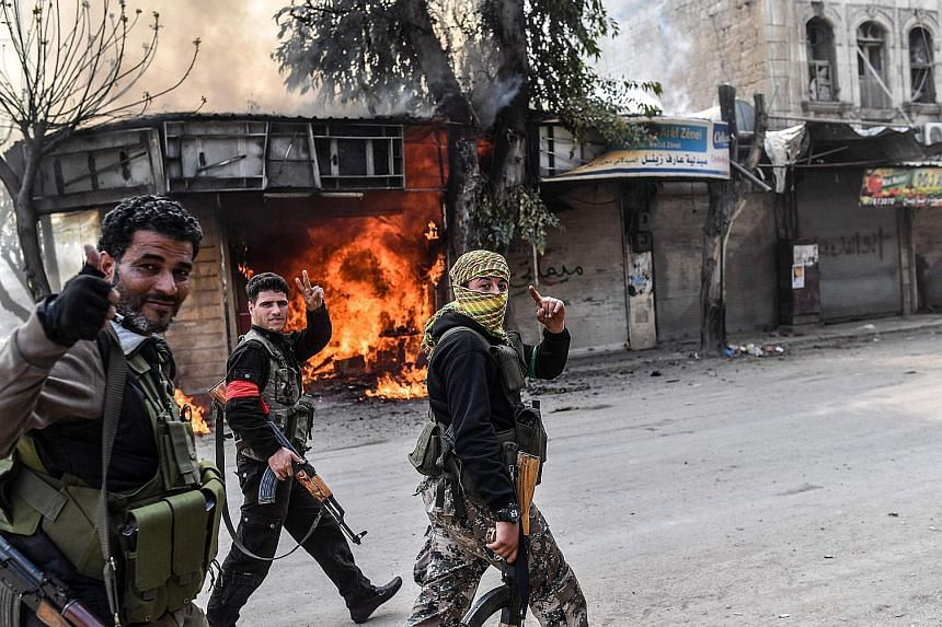 Turkish-backed Syrian rebels walking past a burning shop in the city of Afrin in northern Syria yesterday.