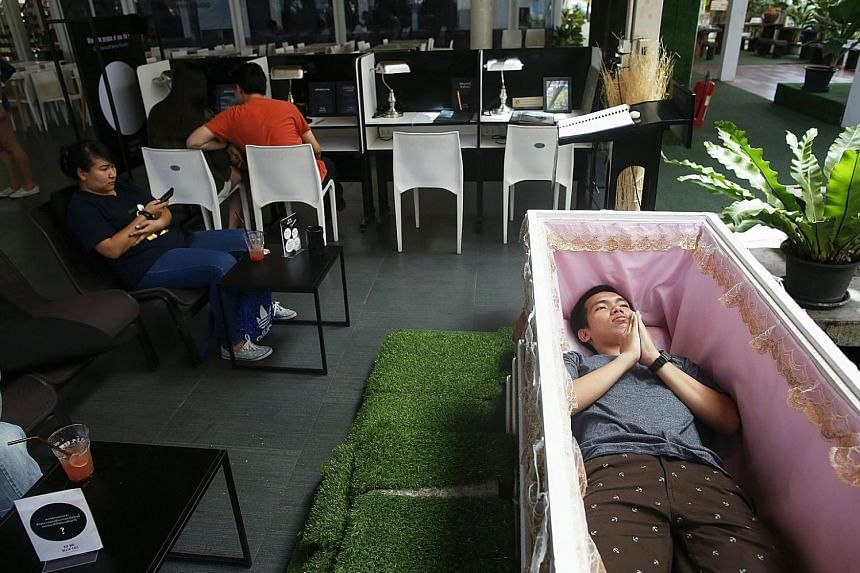 Thai customer Thanawit Suthapanya, 24, prays as he lies inside a coffin in Kid Mai Death Cafe (Rethink Death Cafe) in Bangkok, and no wonder, because he might as well be at his own funeral. The experience he had yesterday was a strange and eerie one,
