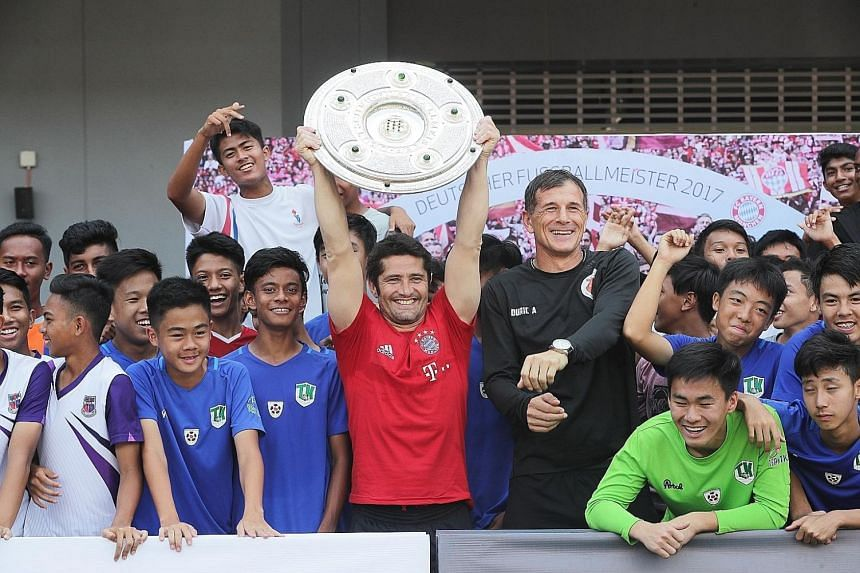 Bixente Lizarazu lifting the Bundesliga Champions Shield, won by his former team Bayern Munich for the past five seasons, alongside principal of the ActiveSG Football Academy Aleksandar Duric and participants of the FC Bayern Youth Cup Singapore. Wat