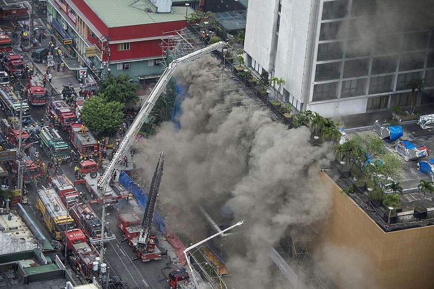 Above: A fireman receiving first aid from colleagues. He had been rescued after being trapped by thick smoke as he battled a fire that engulfed Waterfront Manila Pavilion, a high-rise hotel and casino complex yesterday. Left: Firemen fighting the fla