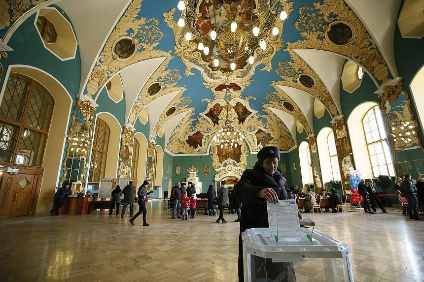 A voter casts her ballot inside a Kazansky railway terminal building in Moscow yesterday. The Kremlin is seeking high participation to give legitimacy to President Vladimir Putin's inevitable fourth term.