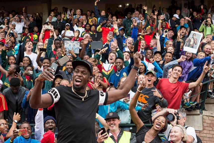 Retired Jamaican Olympic and World champion sprinter Usain Bolt poses for a photo with spectators at the Ruimsig Stadium in Johannesburg, on Jan 29, 2018.