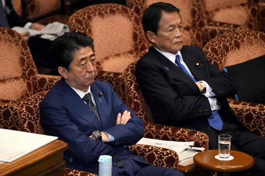 Japan's Prime Minister Shinzo Abe (left) and Finance Minister Taro Aso attend a upper house budget committee session at parliament in Tokyo, on March 14, 2018.