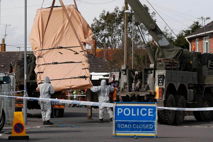 British Military personnel removing a vehicle connected to the March 4 nerve agent attack in Salisbury, from a residential street in Gillingham, southeast England, on March 14, 2018.