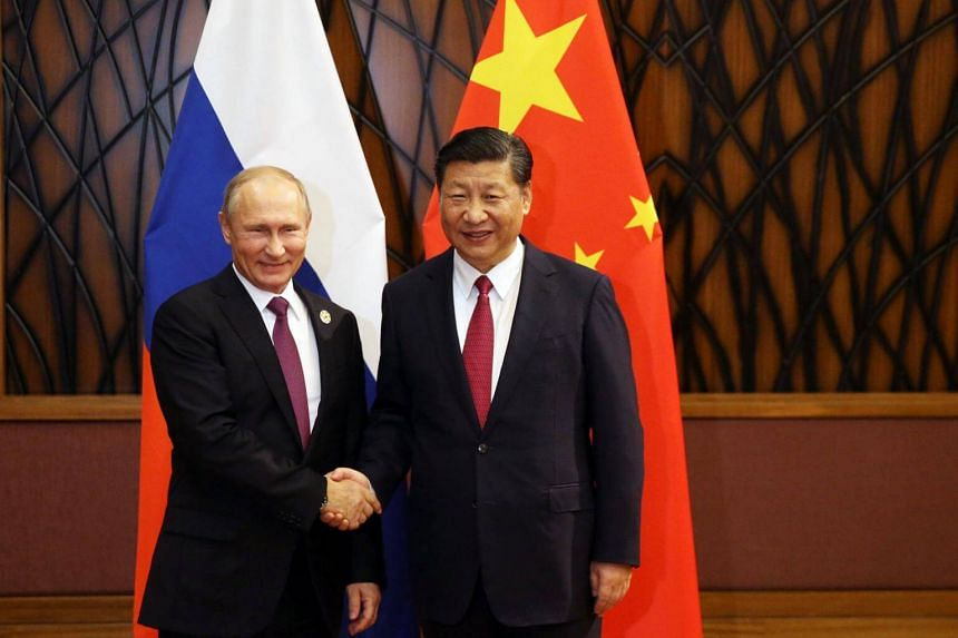 Russian President Vladimir Putin (left) and Chinese President Xi Jinping shake hands during a meeting on the sidelines of the Apec summit in Danang, Vietnam, on Nov 10, 2017.