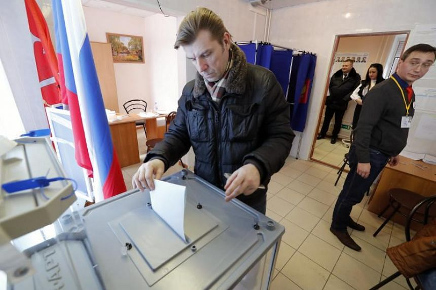 A man casts his ballot while voting in the Russian Presidential elections at a polling station in St. Petersburg, Russia, on March 18, 2018.