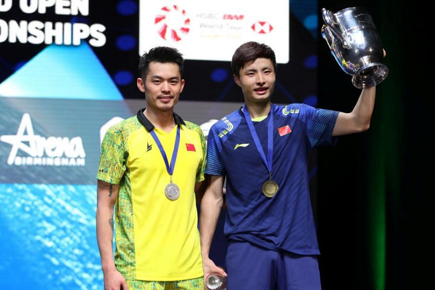 China's Shi Yuqi celebrates victory in the men's singles final alongside losing compatriot Lin Dan in the Yonex All England Open Badminton Championships in Arena Birmingham in Britain on March 18, 2018.