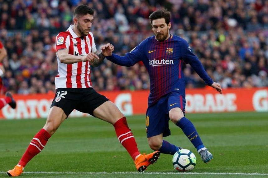 Athletic Bilbao's Spanish defender Unai Nunez (left) vies with Barcelona's Argentinian forward Lionel Messi during the Spanish League football match between FC Barcelona and Athletic Club Bilbao at the Camp Nou stadium in Barcelona on March 18, 2018.