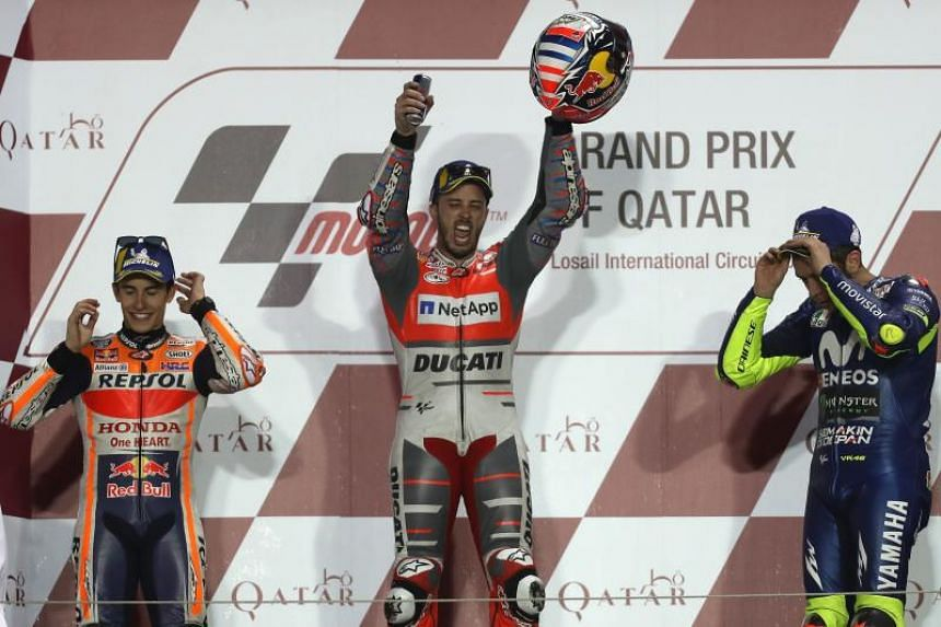 Repsol Honda Team's Spanish rider Marc Marquez (left, 2nd place), Ducati Team's Italian rider Andrea Dovizioso (centre, 1st place) and Movistar Yamaha MotoGP's Italian rider Valentino Rossi (right, 3rd place) celebrate on the podium after winning the