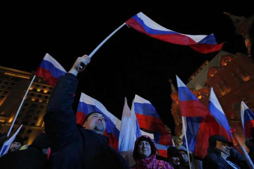 People attend a rally in Manezhnaya Square near the Kremlin during the ongoing presidential elections in Moscow, Russia, on March 18, 2018.