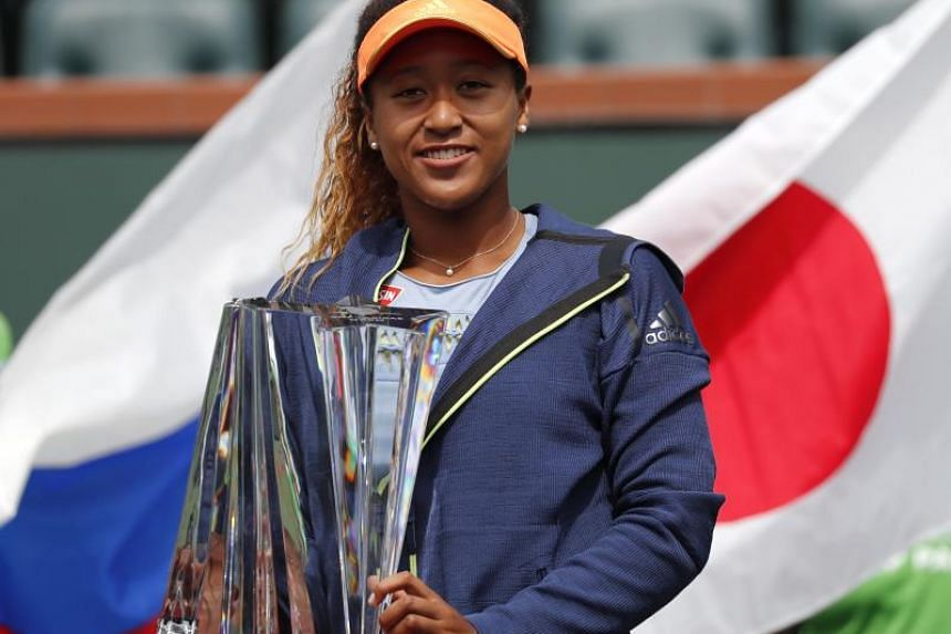 Japan's Naomi Osaka poses with her trophy after defeating Russia's Daria Kasatkina during the BNP Paribas Open Finals at the Indian Wells Tennis Garden in Indian Wells, California, US, on March 18, 2018.