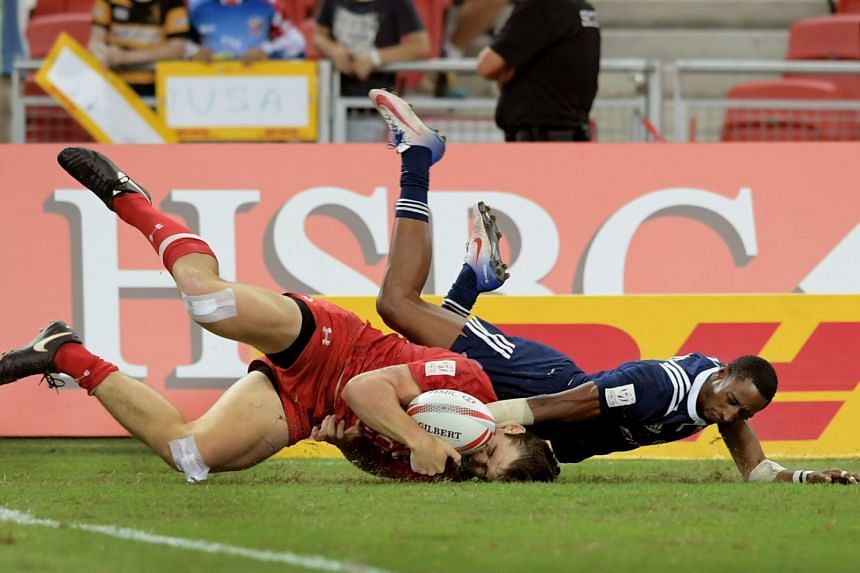 Canada's Matt Mullins, challenged by the US' Perry Baker, scoring the first try. Baker scored two tries but Canada beat the Americans 26-19 in the final of HSBC Singapore Rugby 7s at the National Stadium on April 16, 2017.