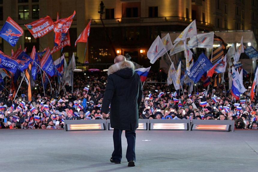 Vladimir Putin attends a rally and concert marking the fourth anniversary of Russia's annexation of the Crimea region, at Manezhnaya Square in central Moscow, Russia, on March 18, 2018.