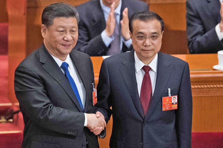 China's President Xi Jinping (left) congratulating Premier Li Keqiang after he was re-elected for a second term, at the National People's Congress held in the Great Hall of the People in Beijing yesterday.