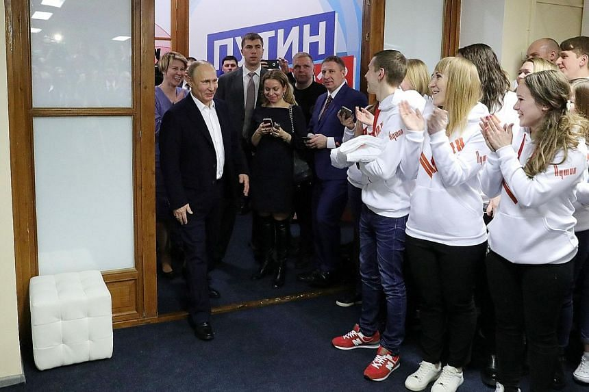President Vladimir Putin visiting his campaign headquarters in Moscow late on Sunday after his win. He recorded his best-ever election performance with 76.67 per cent of the vote, but rejected the possibility of staying in power indefinitely.