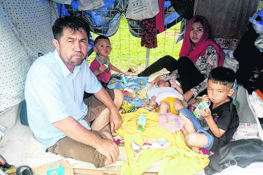 Above: A tent city has sprung up outside the detention centre, with refugees clamouring to get in. Right: Afghan Zabihullah Nazari with his family in their makeshift shelter. They arrived in Jakarta nearly four years ago but ran out of money. Outside
