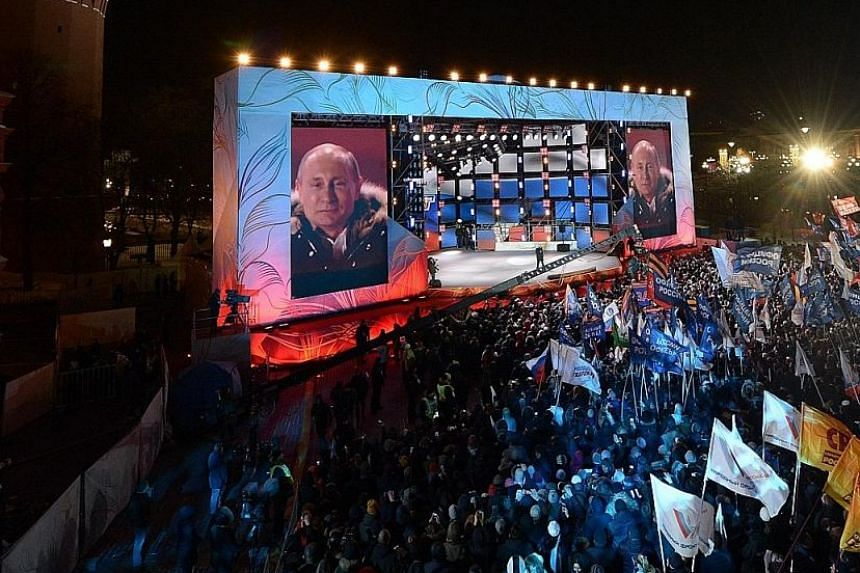Russian President Vladimir Putin speaks to his supporters during a rally at Manezhnaya Square near the Kremlin in Moscow on Sunday. In a late-night victory speech near Red Square after the results were announced, Mr Putin told a cheering crowd the wi
