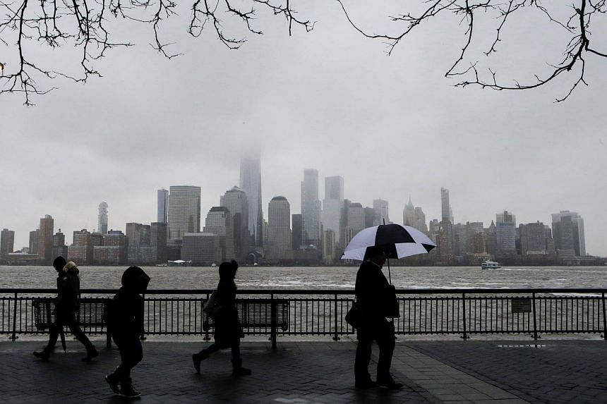 People walking in the rain with the New York skyline in the background on March 7, 2018.