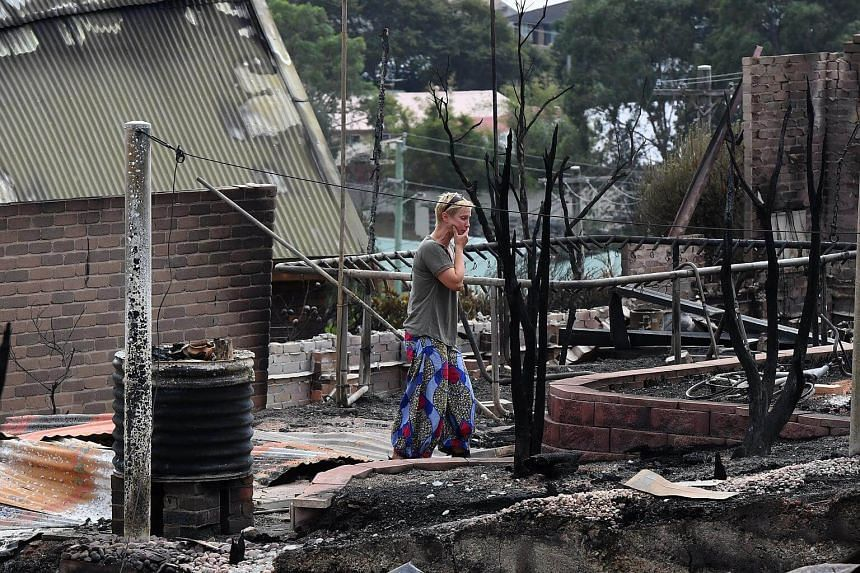 A resident wanders through the burnt out remains of her Wildlife Drive home in Tathra, Australia, on March 20, 2018.
