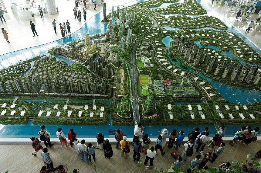 Prospective buyers look at a model of the development at Country Gardens' Forest City showroom in Johor Bahru, Malaysia, on Feb 21, 2017.