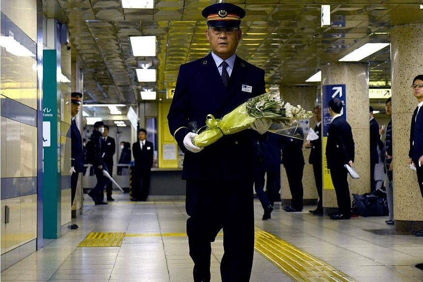 Kasumigaseki subway station manager Toyohiko Otomo walks with a bouquet of flowers towards an alter to mourn the victims of the 1995 sarin gas attack on March 20, 2018.