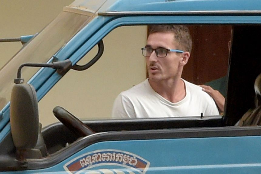 """Daniel Jones, on trial for promoting a pool party with images deemed """"pornographic"""", is escorted by a prison guard at a court in Siem Reap on March 15, 2018."""