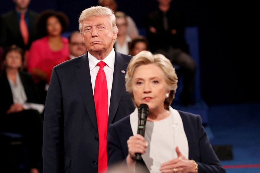 Republican US presidential nominee Donald Trump listens as Democratic nominee Hillary Clinton answers a question from the audience during their presidential town hall debate at Washington University in St. Louis, Missouri, on Oct 9, 2016.