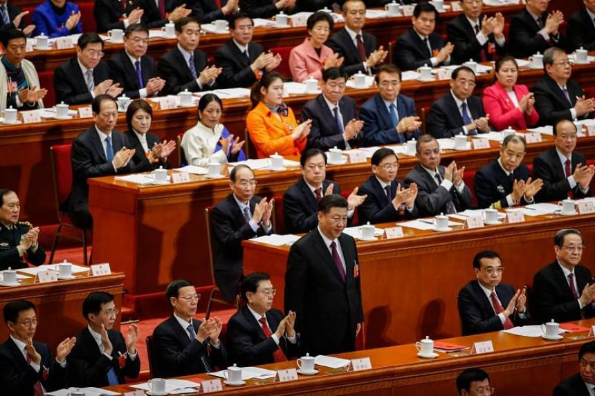 Chinese President Xi Jinping (C) stands after delivering a speech as other delegates applaud him during the closing of the first session of the 13th National People's Congress (NPC) at the Great Hall of the People in Beijing, China, on March 20, 2018