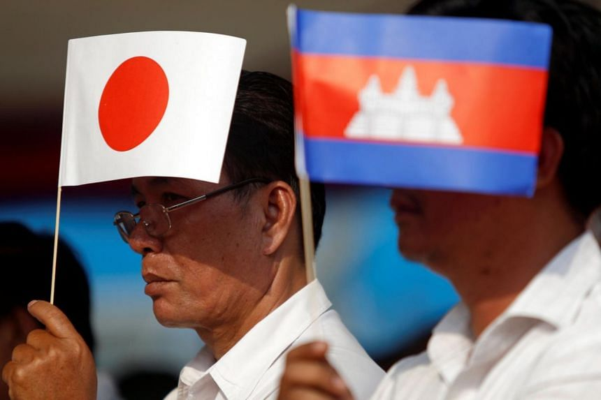 Men hold Cambodian and Japanese flags during the inauguration ceremony of National Road No. 1, which was built with aid from Japan, in Phnom Penh, Cambodia, on March 13, 2018.