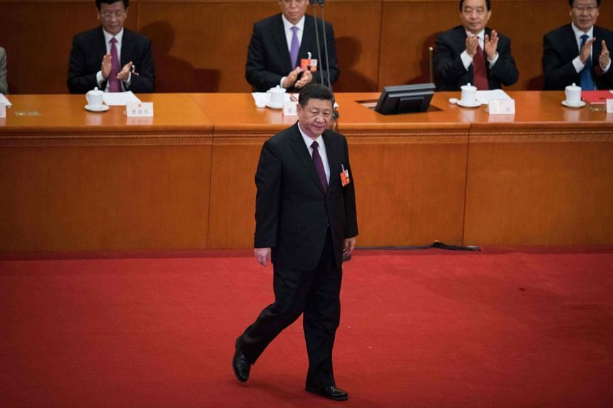Chinese President Xi Jinping walks before he bows to delegates after delivering a speech during the closing session of the National People's Congress at the Great Hall of the People in Beijing on March 20, 2018.