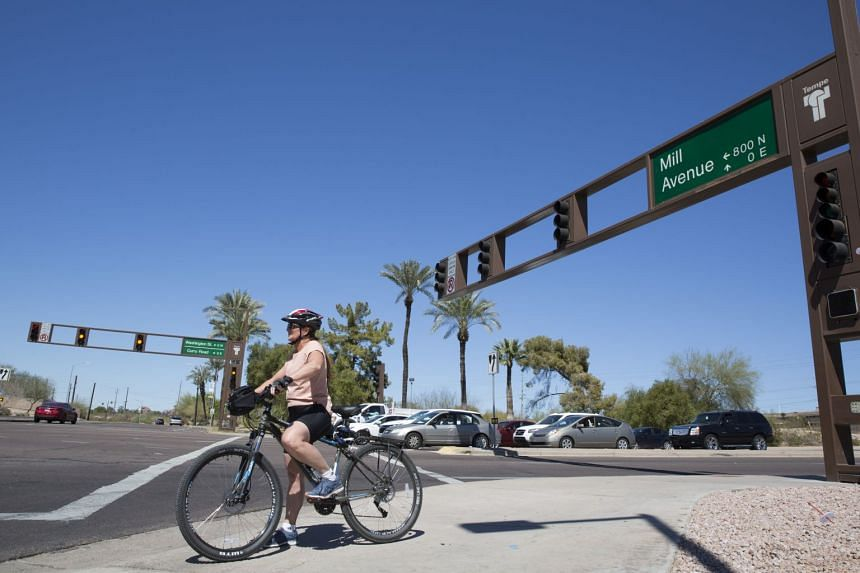 A cyclist waits to cross Mill Avenue at its intersection with Curry Road in Tempe, Arizona, March 19, 2018.