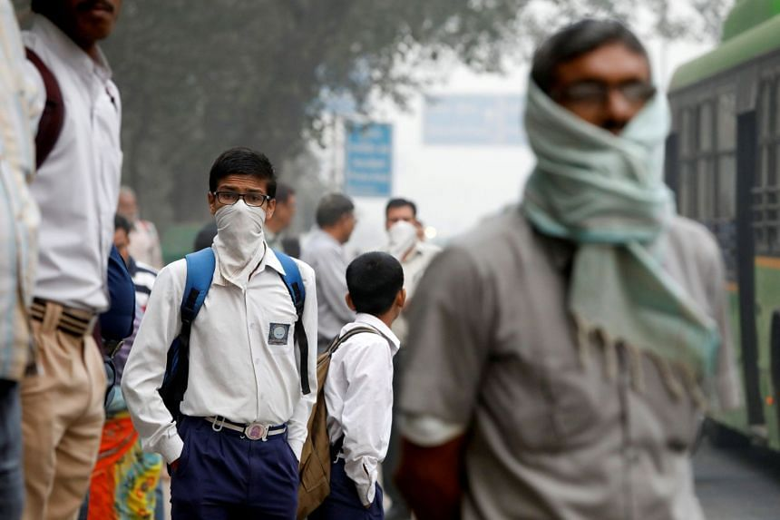 A schoolboy covers his face with a handkerchief as he waits for a passenger bus on a smoggy morning in New Delhi, India, on Nov 8, 2017.