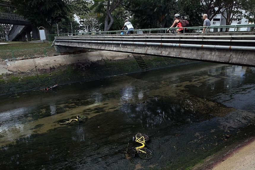 Three shared bikes lying in a canal in Marine Terrace on Monday. Under new rules, users cannot end their rental sessions until their bikes are returned to designated zones.