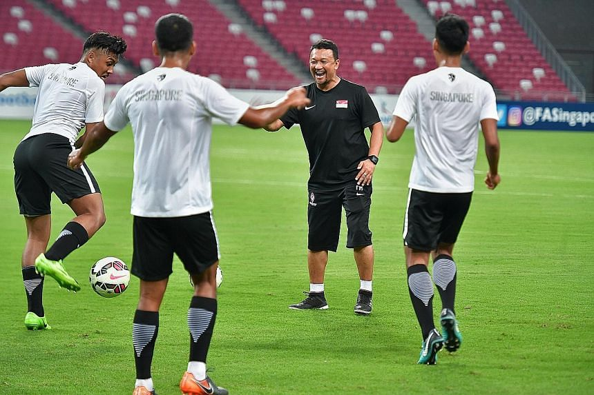 Fandi Ahmad in a relaxed mood with his Singapore players at last night's training session at the National Stadium, ahead of today's clash against Indonesia's Under-23 team.