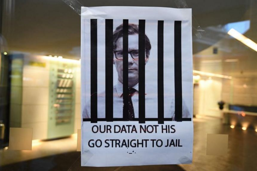 A protester leaves a poster depicting Alexander Nix, chief executive of Cambridge Analytica, outside his office in London on March 20, 2018.