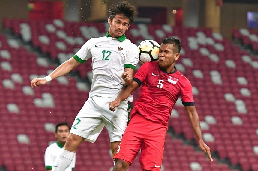 Singapore's defender Shahril Saberin squares off with Indonesia's Gavin Kwan Adsit, also a defender.