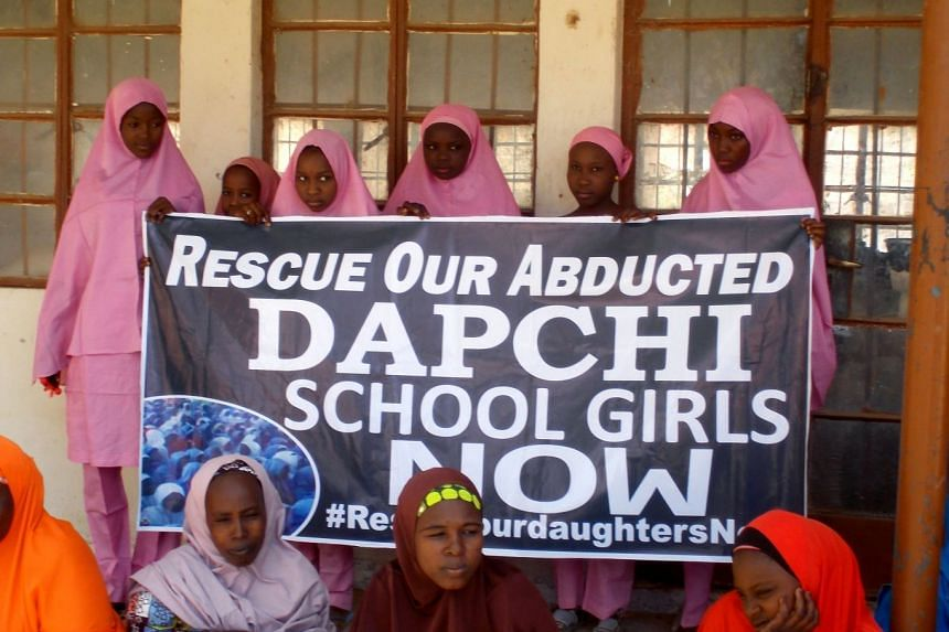 Schoolgirls holding a banner while waiting for the arrival of Nigerian President Muhammadu Buhari at the Goverment girls' science and technical college in Dapchi, Nigeria, on March 14, 2018.