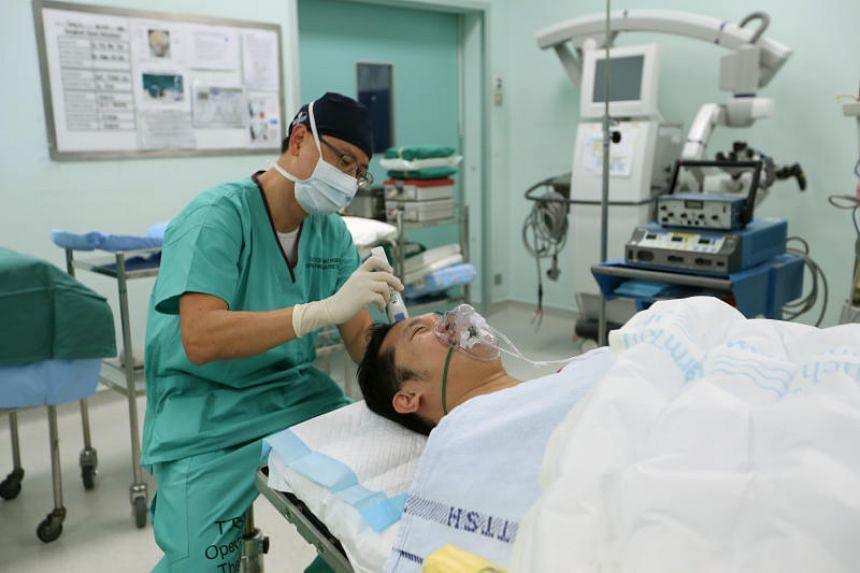 "Neurosurgeon Ng Wai Hoe, medical director of the National Neuroscience Institute, shaving Mr Oh's head after asking him how close a shave he wants. Mr Oh replies: ""Take it all off, it's only hair, it will grow back. I have no regrets."""
