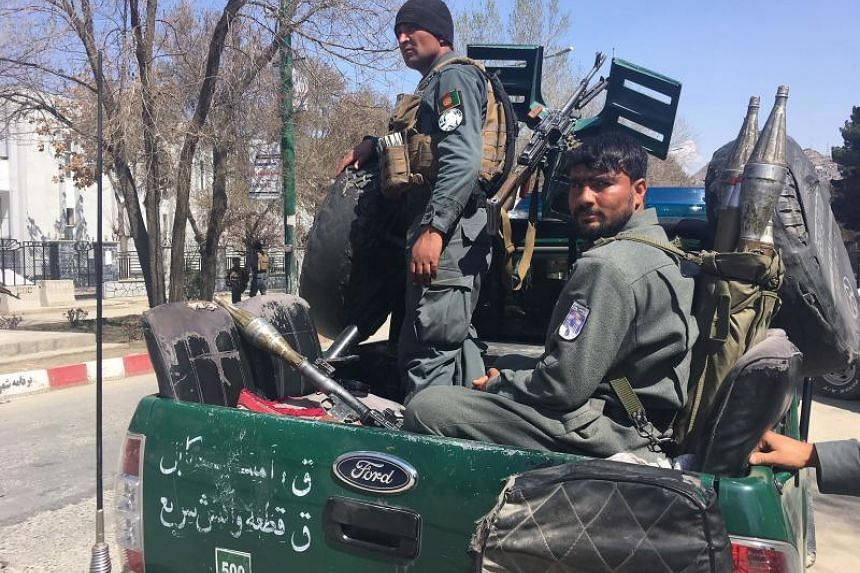 Afghan security forces looking on near the site of a suicide bombing attack in Kabul on March 21, 2018. A suicide bomber blew himself up in front of the Kabul University, officials said, as Afghans celebrate the Persian new year holiday.