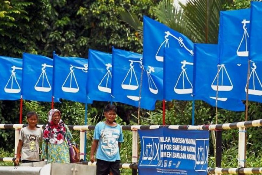 Pedestrians walking past a line of Barisan Nasional flags and banner in Malaysia.