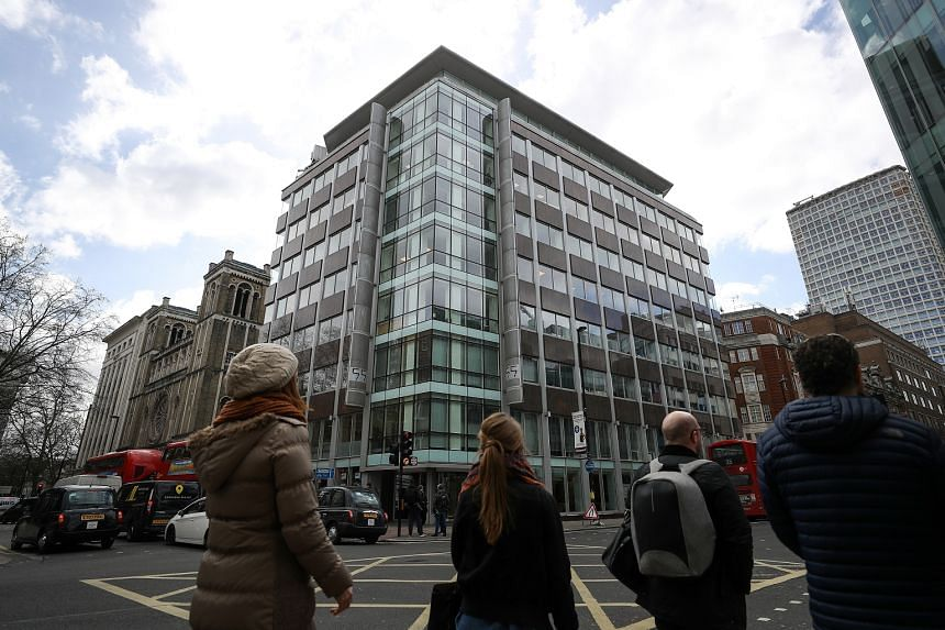 Pedestrians pass the building that houses the offices of Cambridge Analytica in London on March 20, 2018.