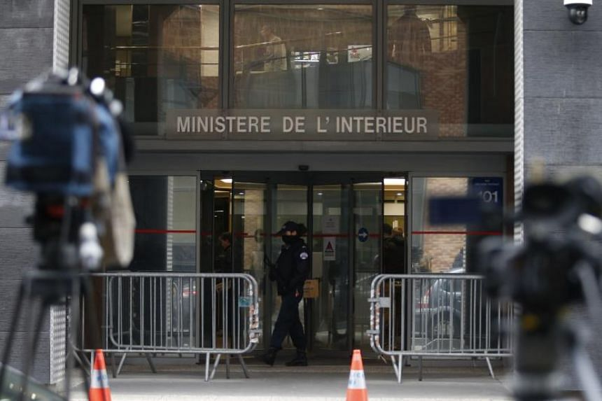 A police officer stands guard outside the headquarters of the Central office for the fight against corruption and financial and fiscal crime on March 21, 2018 in Nanterre, outside Paris, during the police custody of the French former president.