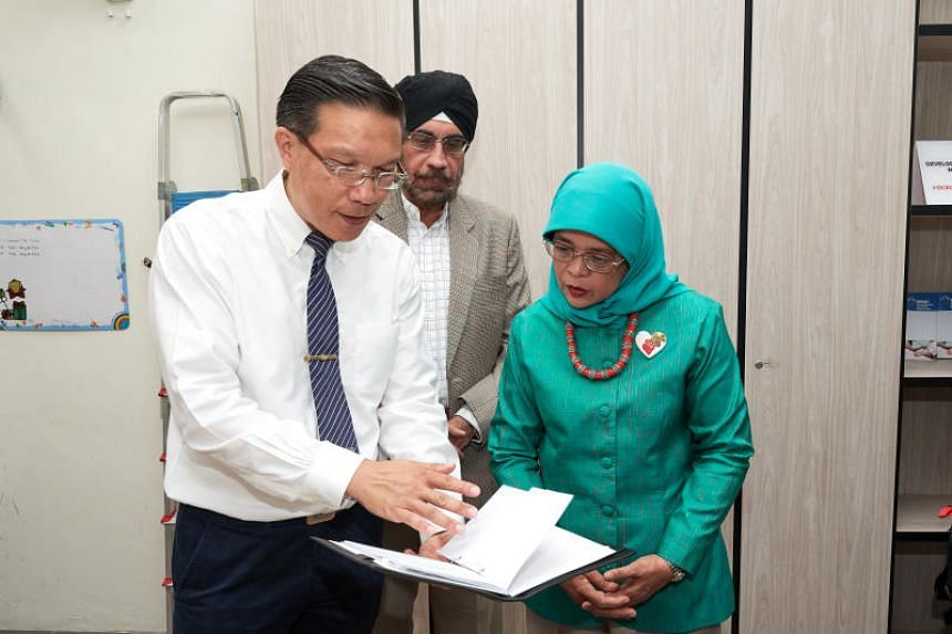 "Dr Edwin Lim (left) and Dr Balbir Singh (centre) show President Halimah a ""health passport"" issued to patients at the clinic that contains detailed medical records that general practitioners can refer to."