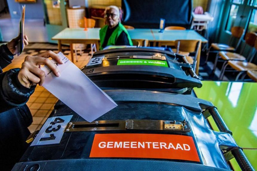 Voters cast their vote during the Dutch municipal elections at a polling station in a theatre in Rotterdam, Netherlands, on March 21, 2018.