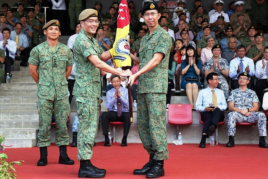 Major-General Melvyn Ong Su Kiat (centre) handing over the command symbol to Brigadier-General Goh Si Hou at a ceremony at Pasir Laba Camp yesterday. BG Goh takes over as Chief of Army from MG Ong, who had held the position since 2016. BG Goh, 40, pr